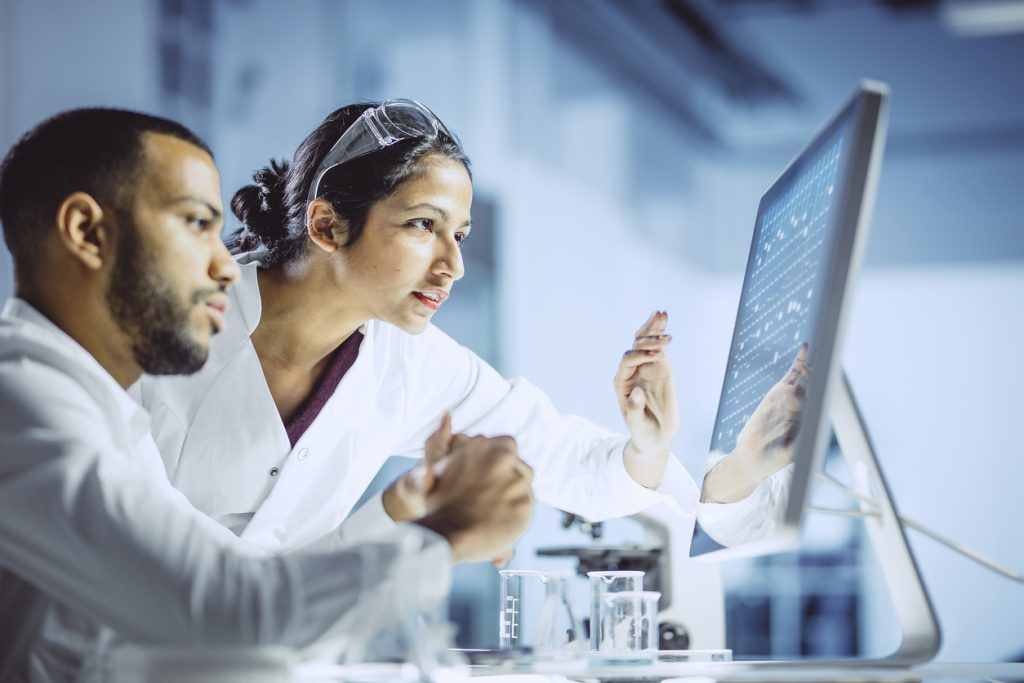 Two clinical researchers analyzing information on a computer