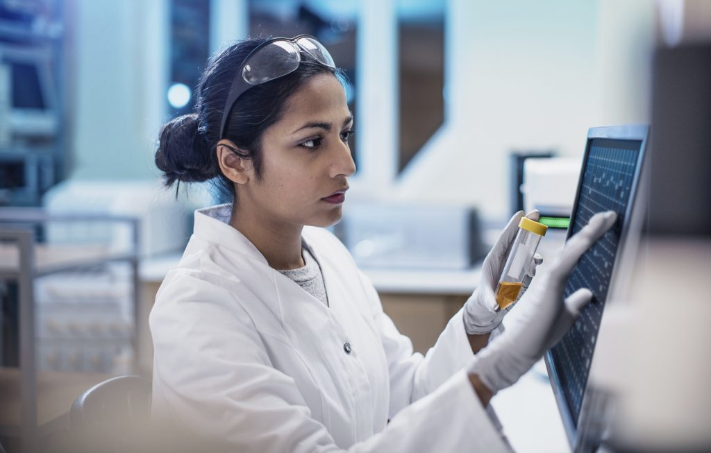clinical researcher studying data on a computer screen